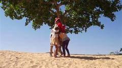 WS Kids hugging embracing and huddling in sand desert with Santa hats under a tr Stock Footage