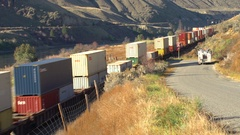 Railroad, container train, high angle with river in bg, arid autumn day Stock Footage