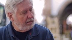 An older mature man in his 70s talking while outside - room for text Stock Footage