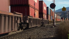 Railroad, container train, low angle at level crossing, arid autumn day Stock Footage