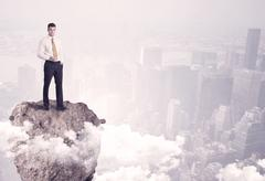 Winner business person standing on rock Stock Photos