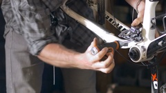 A man tightens the front derailleur on a mountain bike with a screwdriver Stock Footage