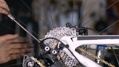 A bike mechanic fine tunes the gears of a mountain bike Stock Footage