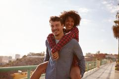 Joyful young girl getting a piggy back as she smiles a toothy smile Stock Photos