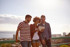 Three friends smiling at a tablet with very bright late afternoon Stock Photos