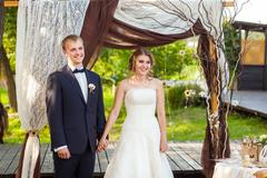 Couple during wedding ceremony under arch Stock Photos
