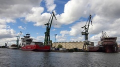 Industrial Shipyard Cranes Harbour And Buildings Seen From A River Stock Footage