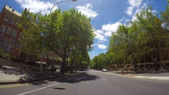 Vehicle POV driving along scenic street past University buildings Stock Footage
