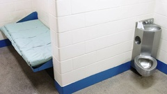 A prison jail cell with bed and toilet Stock Footage