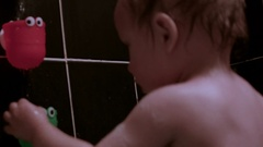 Close up Video of Caucasian Toddler Boy playing With Bath Toys Attached To The W Stock Footage