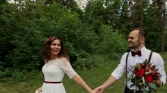 Beautiful pair of hipsters walking in a summer forest. Holding hands. Smile. Stock Footage