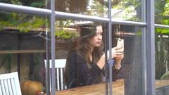 Girl sitting near the window and looking at the phone Stock Footage