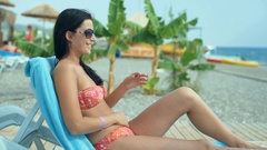 A young woman in a swimsuit relaxing on a deckchair on the beach. Stock Footage