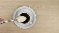 Hand putting spoon sugar into a cup of coffee and stirring it to lay down the Stock Footage