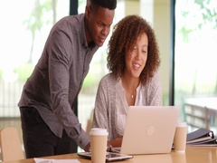 Young happy co-workers using a computer Stock Footage