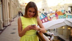 Young beautiful woman in yellow dress reads message on phone Stock Footage