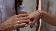 Hands of lovers. Man's hand stroking a woman's hand wearing ancient bracelet. Stock Footage