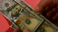 Take US Dollars Banknotes On Red Table. Sunny Day Stock Footage