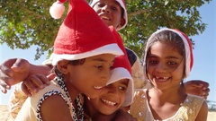 Close up of kids smiling and laughing with Santa hats in summer in sandy desert Stock Footage