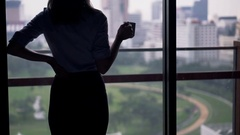 Young businesswoman drinking coffee and admire view from window at home Stock Footage