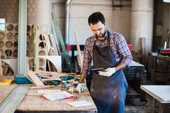 Portrait of a carpenter standing in his woodwork studio and holding digital Stock Photos