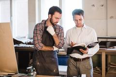 Happy male carpenter showing something to coworker at his notebook papers in Stock Photos
