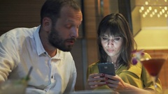 Couple fighting, arguing in cafe, woman using smartphone  Stock Footage
