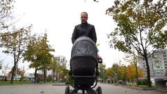 Father in the jacket carries baby carriage with a baby and talking Stock Footage