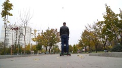 A man with a baby carriage rides away on a gyroscooter in a park Stock Footage