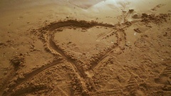 Heart drawn in the sand. Beach sand background with heart. Stock Footage