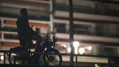 Healthy young man enjoying cycling trip around night city, using mobile app Stock Footage