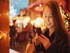 Woman Using Smartphone on European Christmas Market. 4K. Evening Lights Stock Footage
