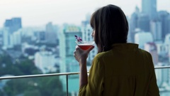 Young woman drinking margarita and admire view standing on terrace Stock Footage