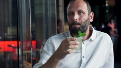 Happy, young man drinking mohito in cafe Stock Footage