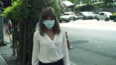 Young woman with mask walking near street in city  Stock Footage