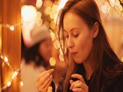 Woman Enjoying European Christmas Market, eating chetnuts. 4K. Evening Lights Stock Footage