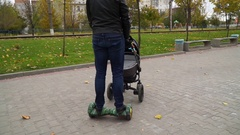 Father walks with a baby carriage and riding on a gyroscooter Stock Footage