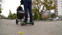 Gyroscooter's and baby carriage's wheels rolling on the sidewalk Stock Footage
