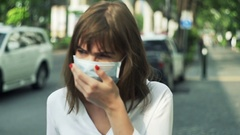Young woman with mask coughing standing near street in city  Stock Footage