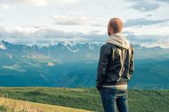 Traveler stay on top of a mountain and looks into the distance. Mountains Stock Photos