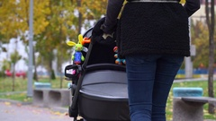 View from the back, as a woman carries a pram Stock Footage