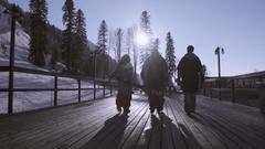 Back side of three skiers walk on road on ski resort. Sun beams. Snowy mountains Stock Footage