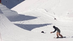 Snowboarder ride on springboard, jump, flip in air. Sunny day. Mountains Stock Footage