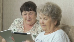 Old women holding the silver digital tablets Stock Footage