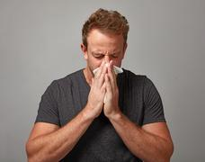 Sneezing man with cold Stock Photos