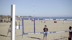 Volleyball game young guy serving team returns ball to net beach Santa Cruz Stock Footage