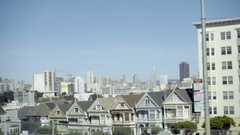 Moving shot of Painted Ladies houses with skyline in background in San Francisco Stock Footage