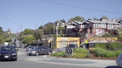Cars driving by houses in Santa Cruz on beautiful sunny day with blue sky Stock Footage