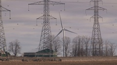 Wind turbines and electricity transmission towers together Stock Footage
