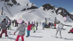 Snowboarders and skiers ride with air balloons in hands. Ski resort. Sunny day Stock Footage